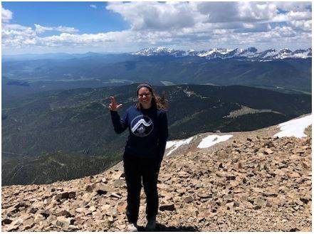 Photo of Colleen on top of a mountain holding up the Laker