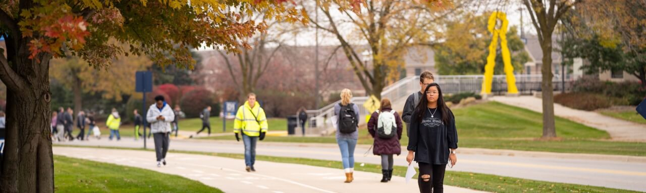 Student walking in front of Mackinac hall, including Parking Services staff