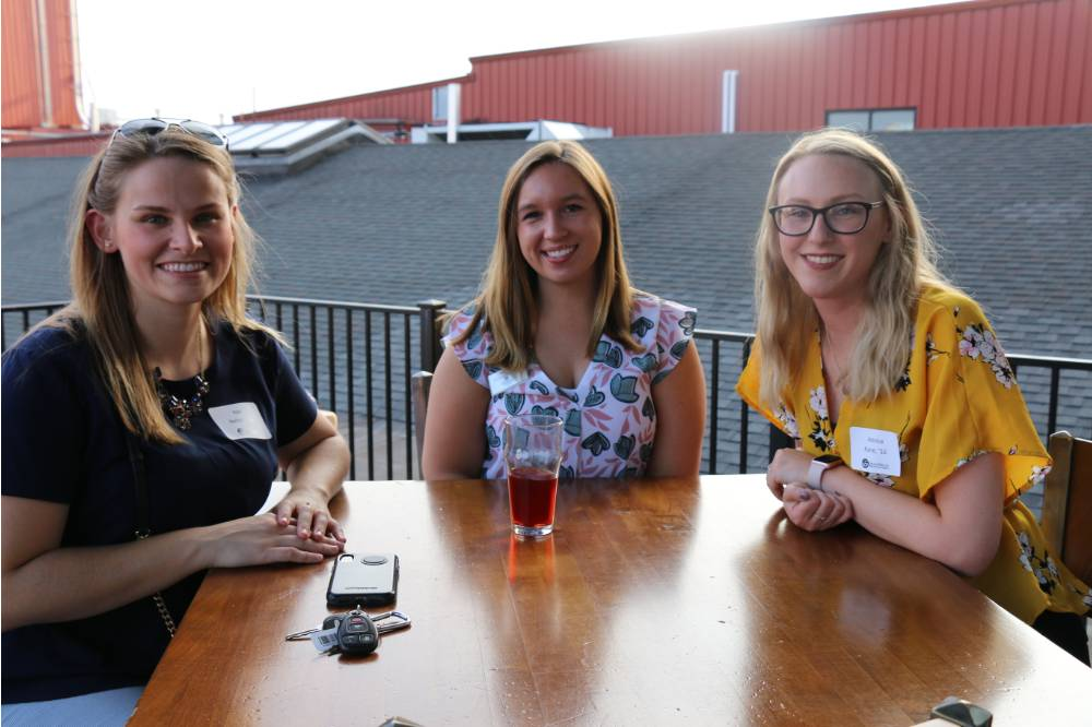 Three alumnae pose for a picture at Founders Brewing Co.