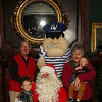 Grandparents and two grandchildren posing with Santa and Louie