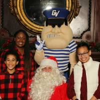 Santa and Louie posing with alumni family of three