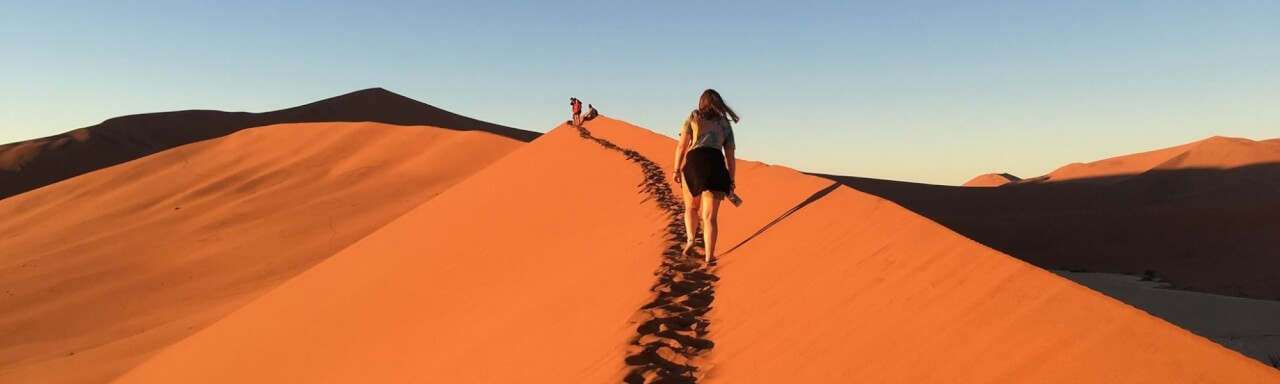 A GVSU student walks along a sand dune in Namibia Africa.