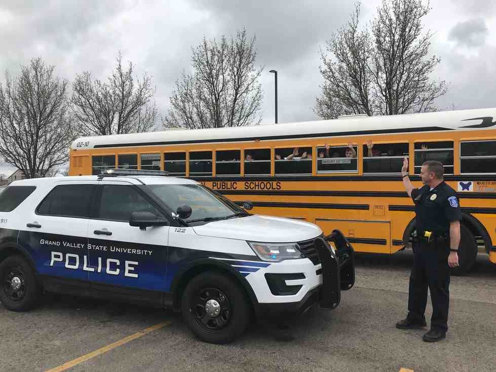 Officers waving at a school bus
