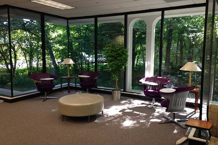 The study space features floor to ceiling windows that look out over the wooded ravine.