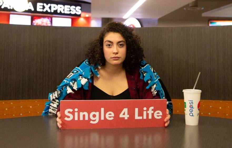 "Student sitting alone at a table with a sign labeled ""Single 4 life"""