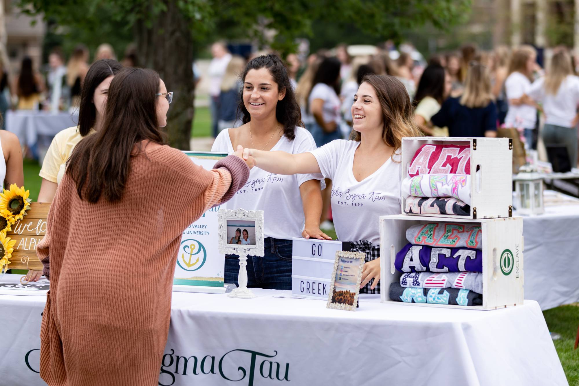 Members of Alpha Sigma Tau meeting a student.