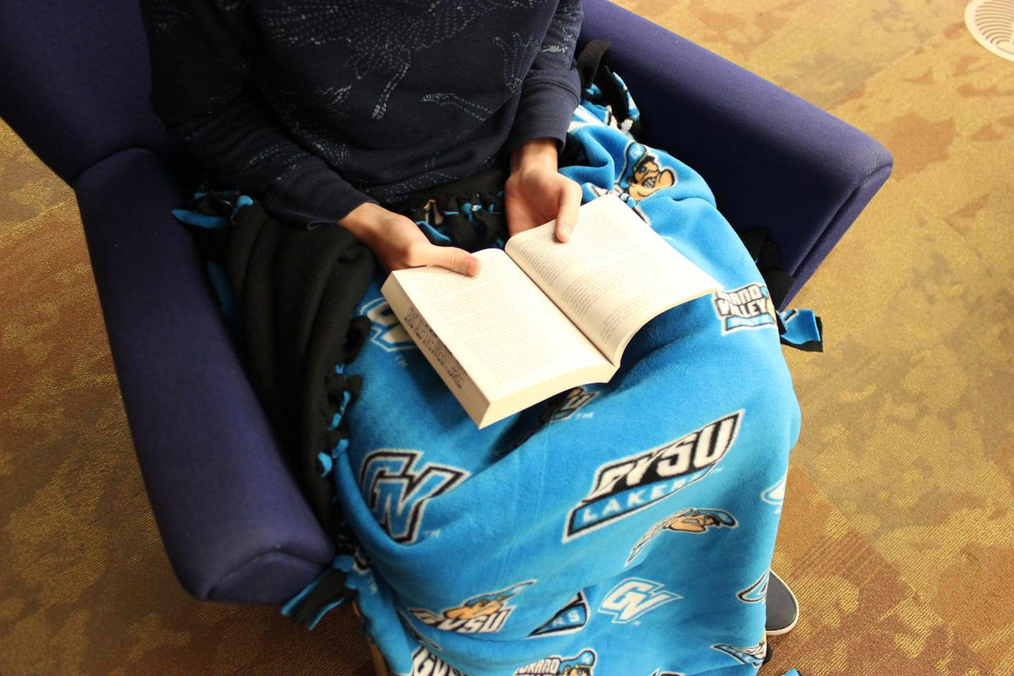 Person reading and wearing gvsu diy blanket