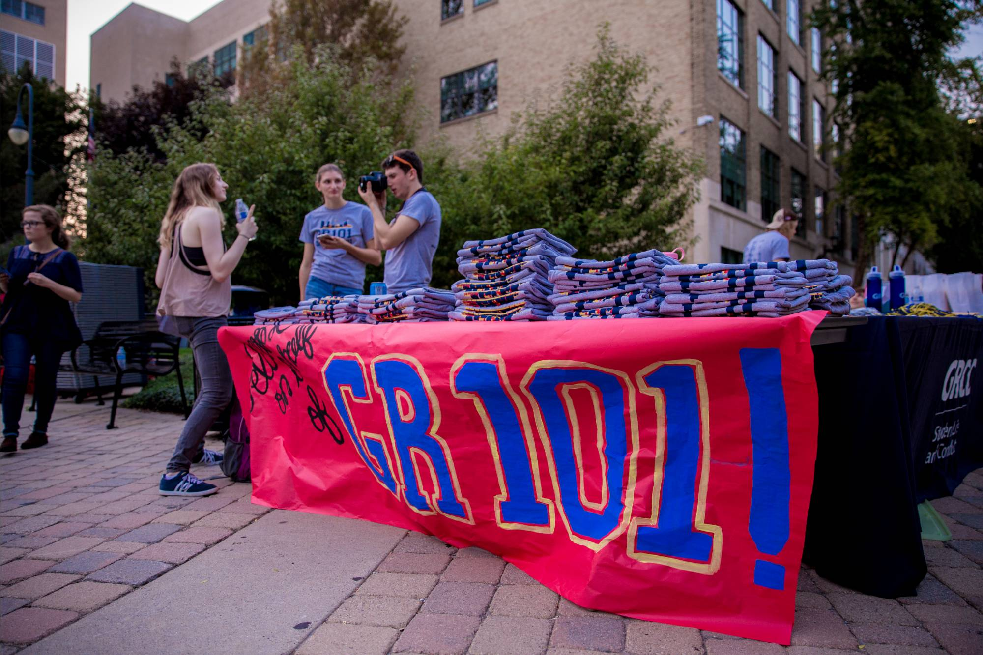 "Table with t shirts and a banner displaying ""GR 101"""
