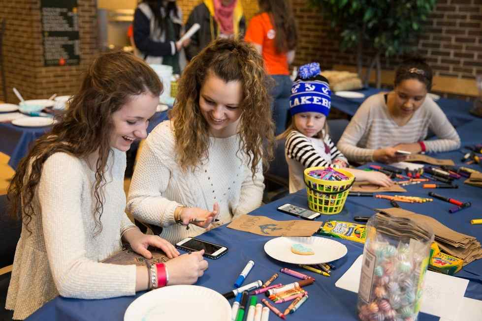 Students doing crafts with young kids at family weekend