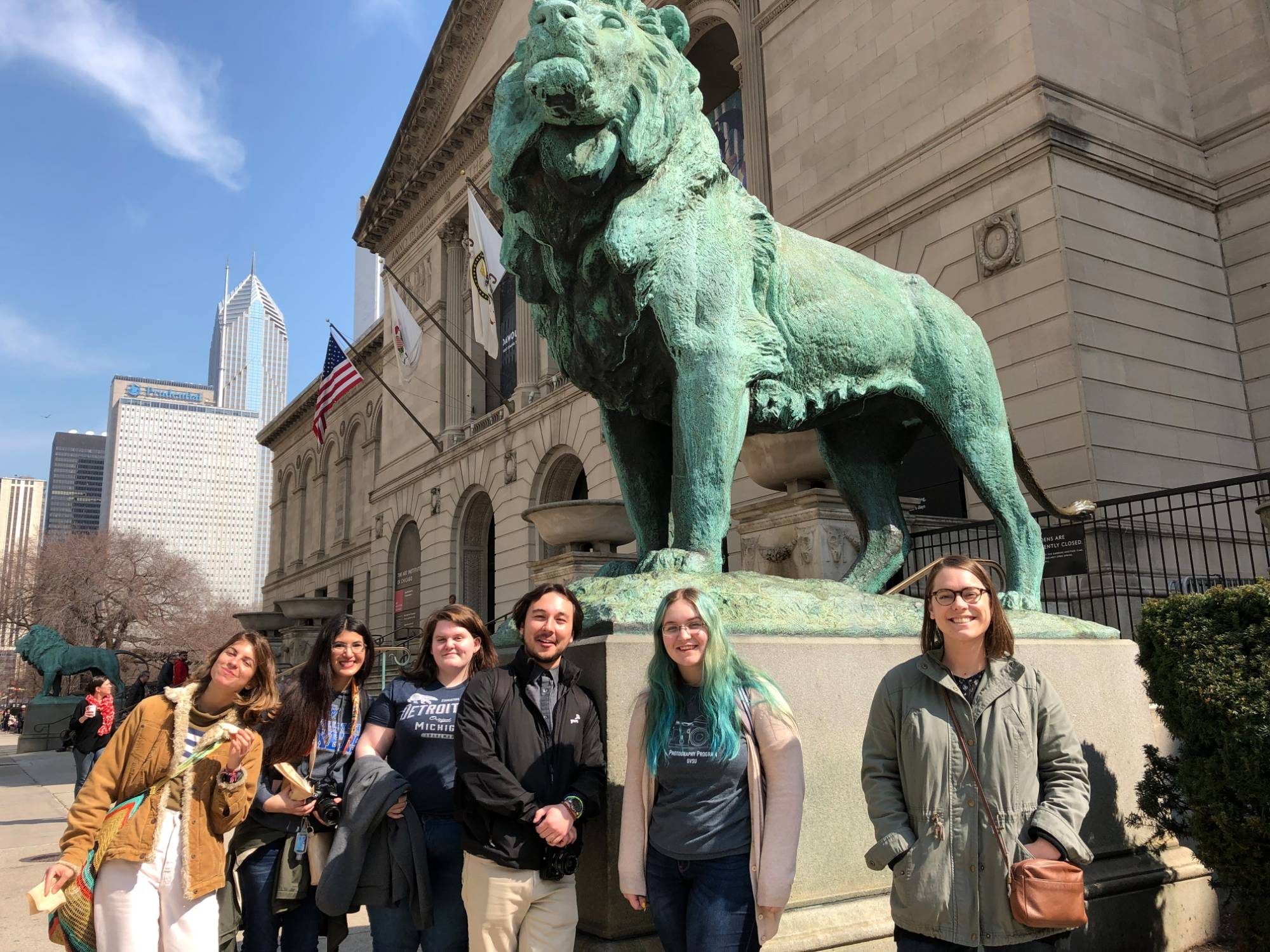 Group of students gathered at the Art Institute by the lion.