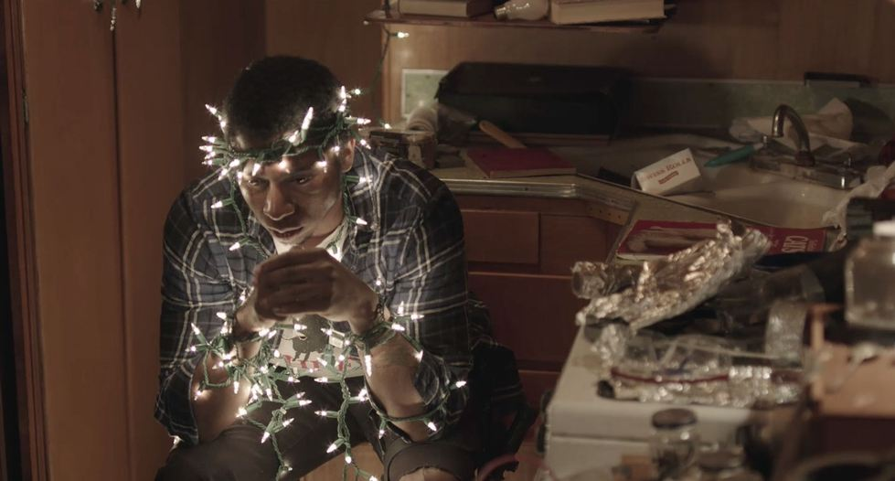 Man sitting in kitchen near a sink wrapped in Christmas lights