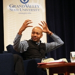 DJ Spooky aka Paul D. Miller with hands raised as if he were putting on a helmet