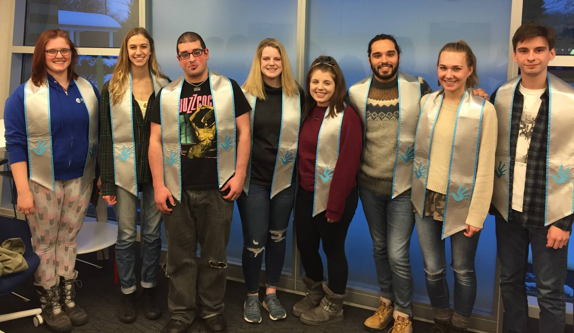 Photograph of 8 students wearing light blue and silver human rights graduation stoles.