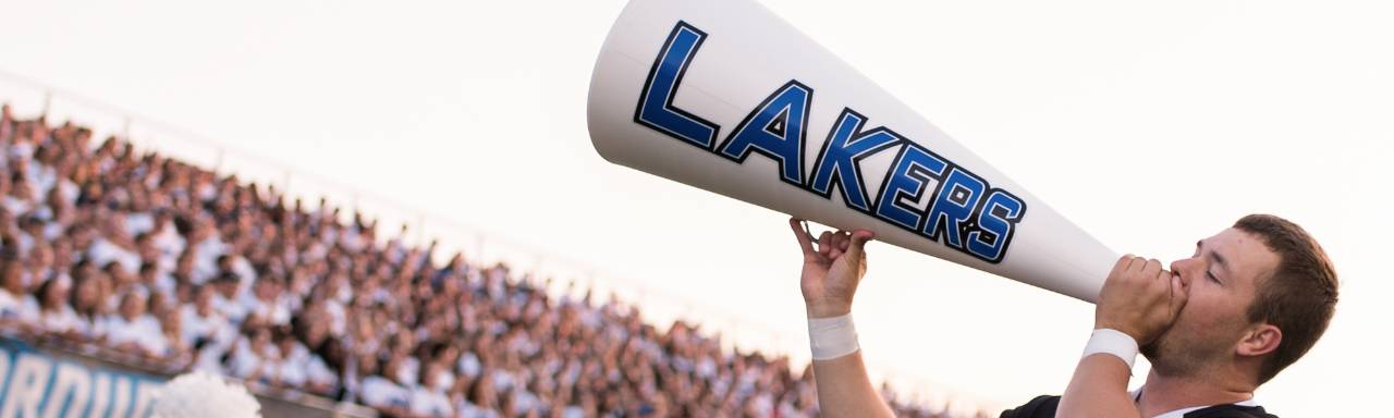 "GVSU cheerleader with megaphone reading ""Lakers"""