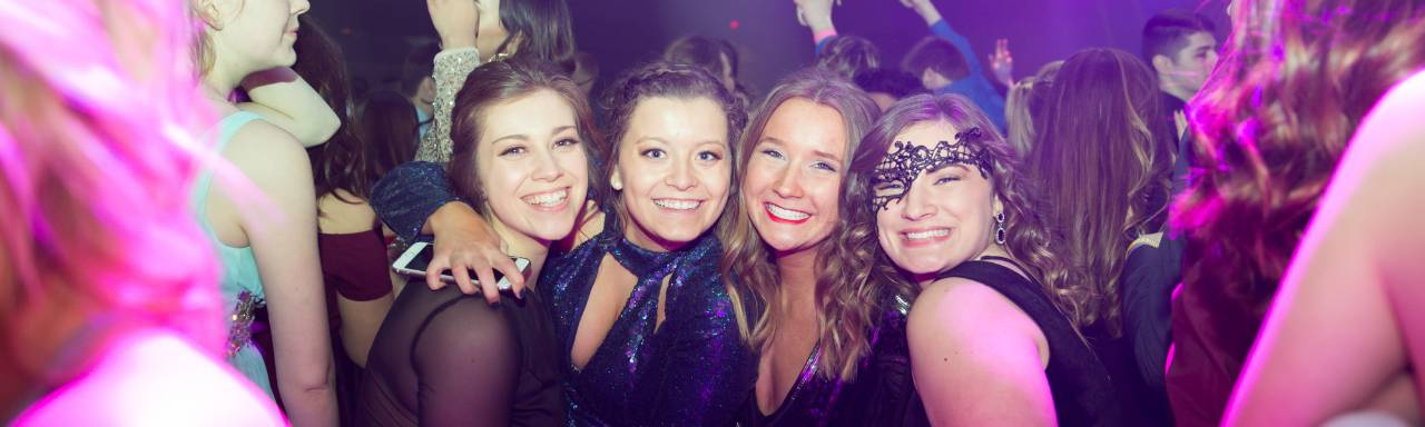 4 GVSU students smiling at Presidents' Ball dance floor