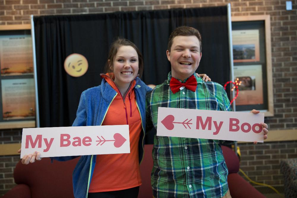 boy and girl posing with signs