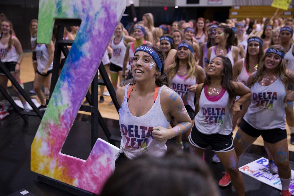 "Sorority sisters wearing ""Delta Zeta"" shirts with paint all over their faces"