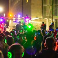 student crowd with colored LED headphones participating in GVSU's silent disco
