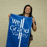 "Girl holding ""We are Grand Valley"" banner"