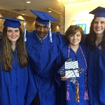 Four graduates in cap and gown