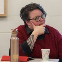 Krista Benson, assistant professor of liberal studies, listens intently to a presentation.