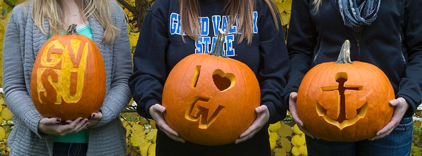 Students holding pumpkins carved with GVSU-themed stencils