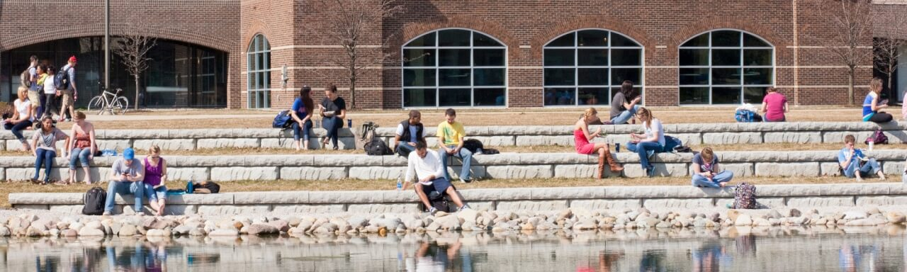 Zumberg pond featuring Kirkhof center in the background and GVSU students sitting near the pond