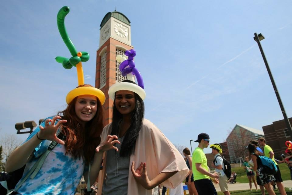 Two students wearing balloon hats in front of the clock tower