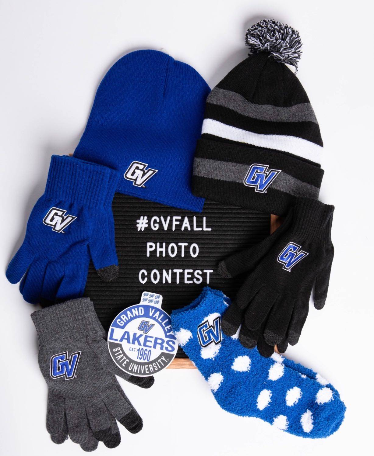 A photo of two GVSU hats, three pairs of gloves, socks and a sticker that are prizes for the #GVFall photo contest.