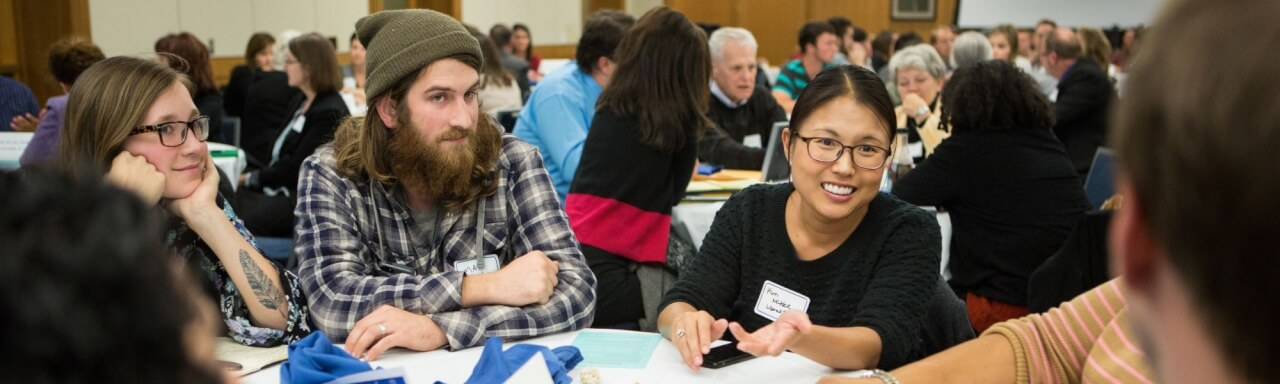 Students and faculty engage in civil discourse at a round table.