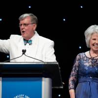 On the Enrichment stage, President Tom Haas makes the Laker hand gesture while Marcia Haas waves.