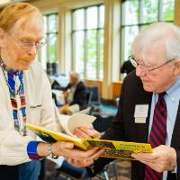 President Emeritus Don Lubbers looking at a book with a guest at the Retiree Reception.