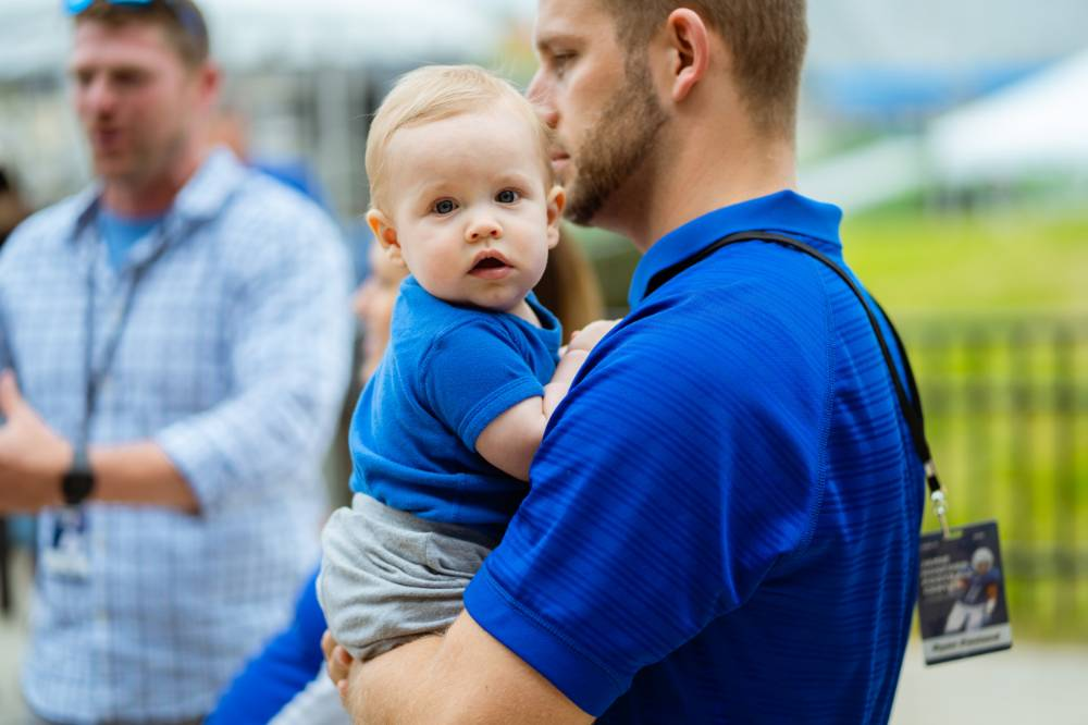 A man holding a baby at the Jamie Hosford Football Center dedication.