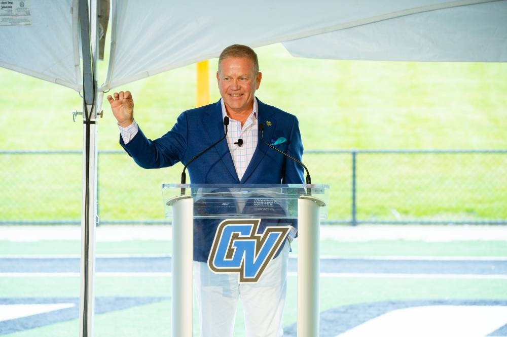 Brian Kelly speaking, holding up a fist at the Jamie Hosford Football Center dedication.