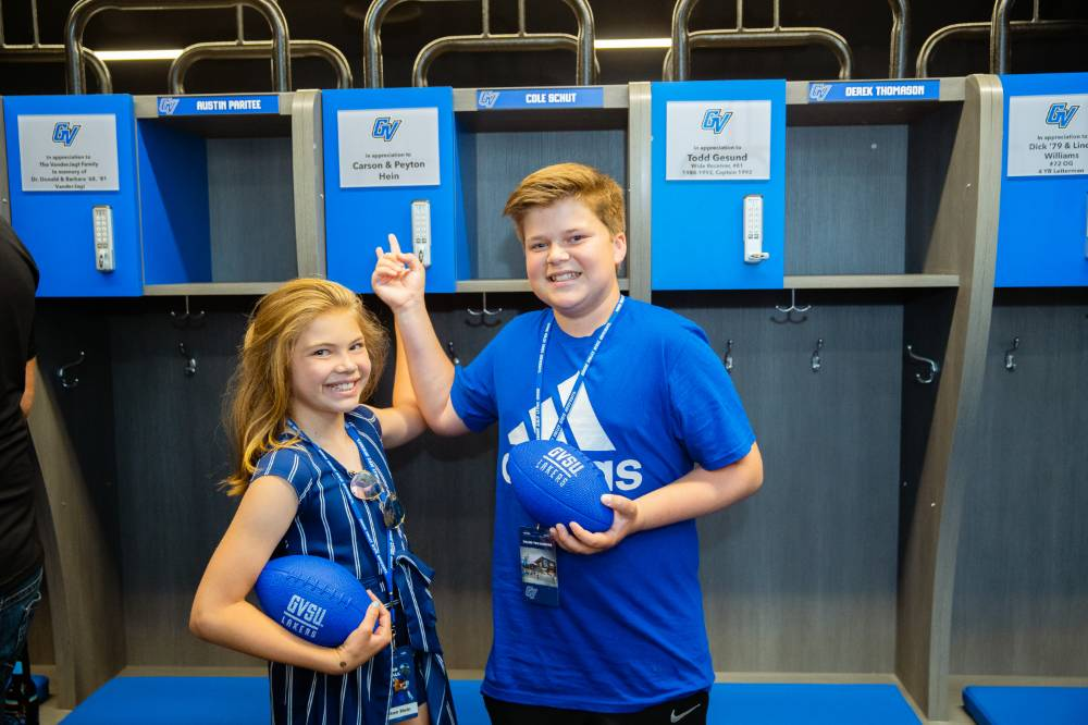 Two children holding footballs, pointing to a named locker at the Jamie Hosford Football Center dedication.