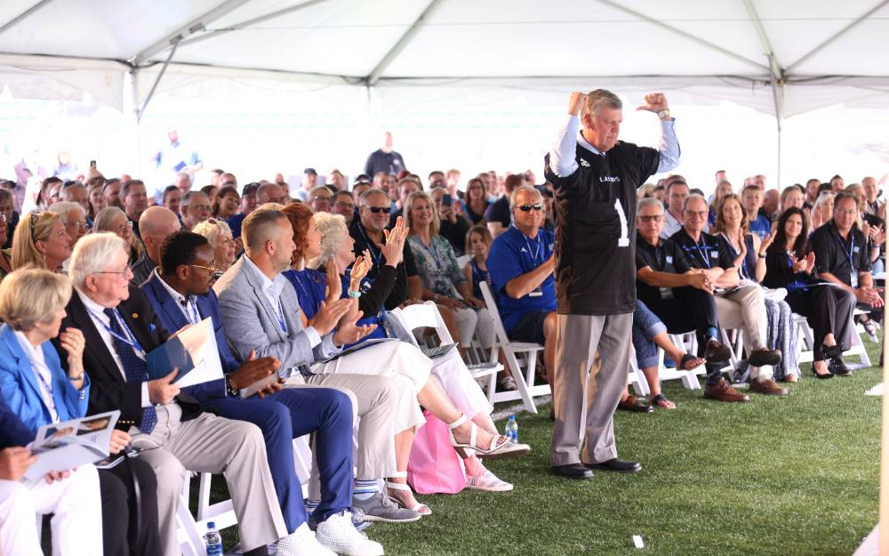 President Tom Haas in front of the crowd at the Jamie Hosford Football Center dedication, pointing to the back of the jersey with his thumbs.
