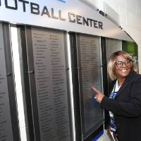 A guest pointing at their name on the donor wall at the Jamie Hosford Football Center dedication.