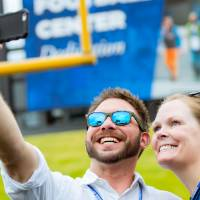 Two guests taking a selfie on the field at the Jamie Hosford Football Center dedication.