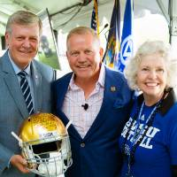 President Tom and Marcia Haas posing together at the Jamie Hosford Football Center dedication. President Haas is holding a golden football helmet.