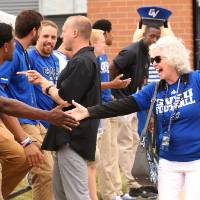 Marcia Haas giving a high-five to a guest at the Jamie Hosford Football Center dedication.