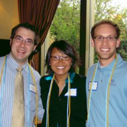 Three people smiling wearing graduation cords