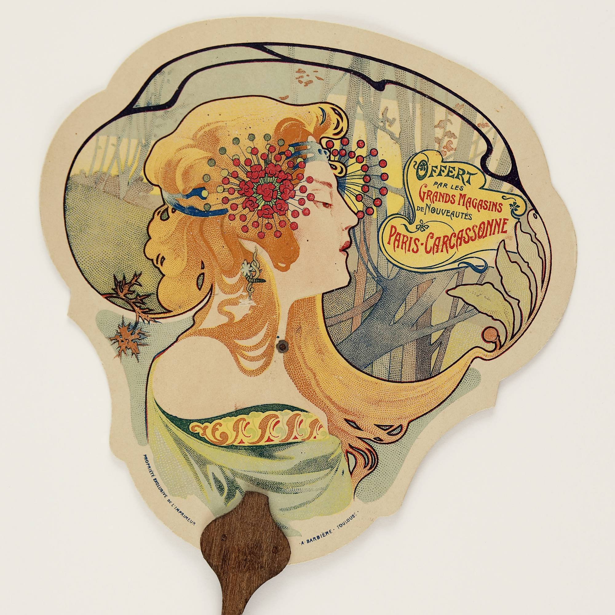 "fan with lithographic print of woman with flowers in her long, orange hair next to text that reads ""Grands Magasins de Nouveautes"""