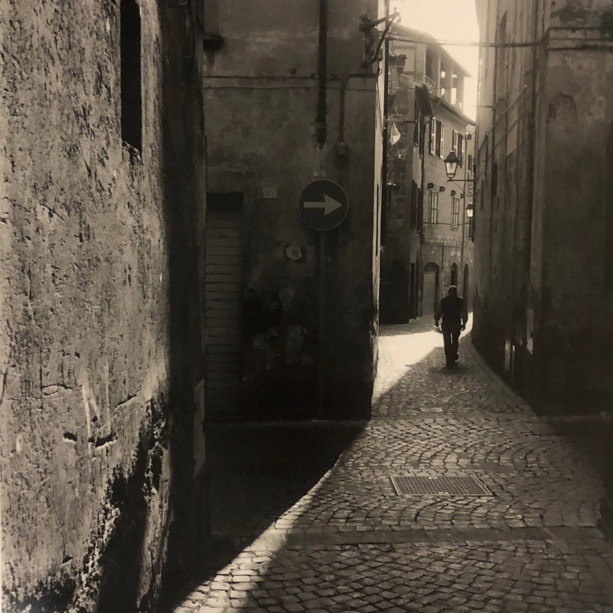 black and white photograph of man's silhouette walking away from viewer in cobblestone alley