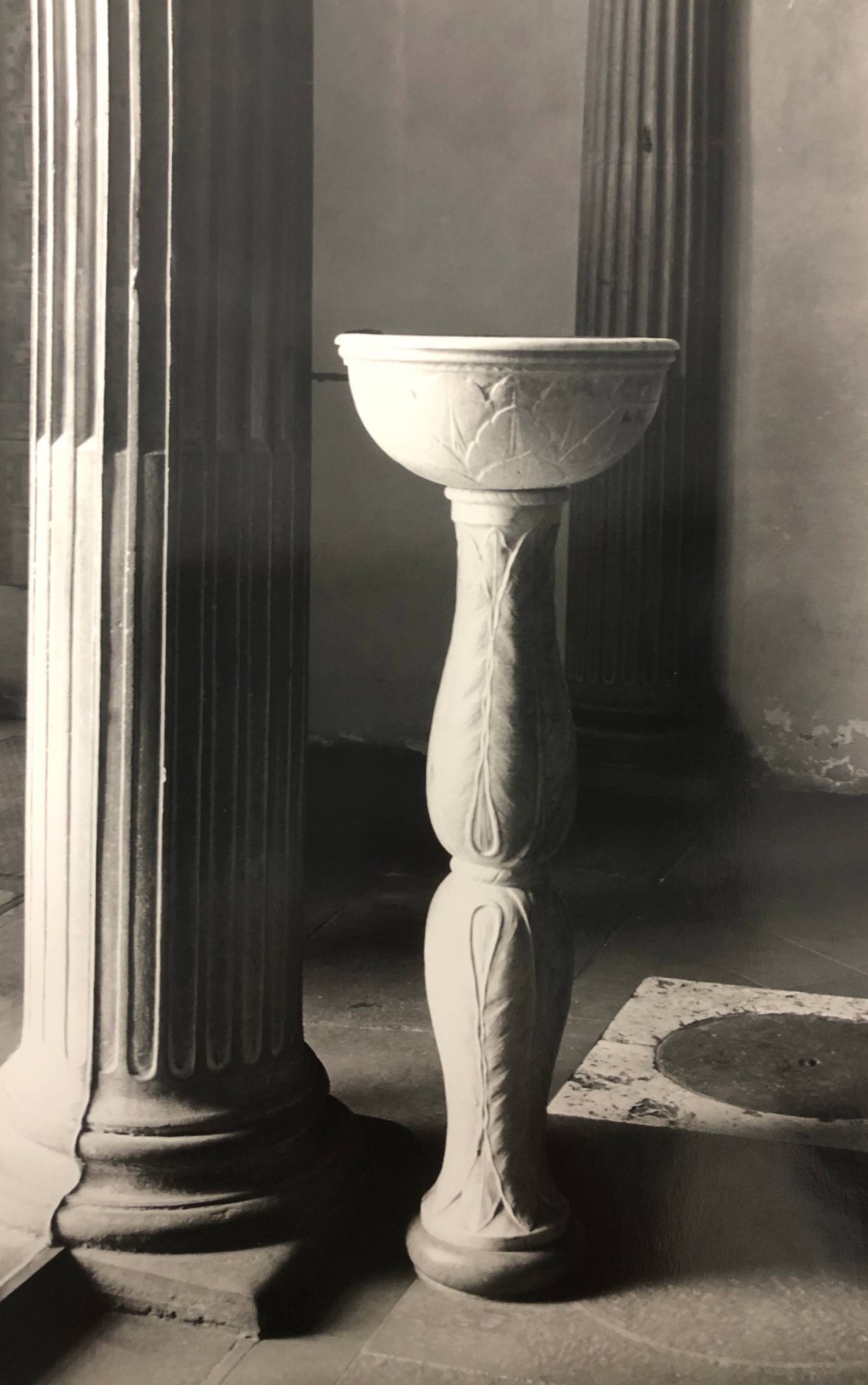 black and white photograph of font of holy water next to column