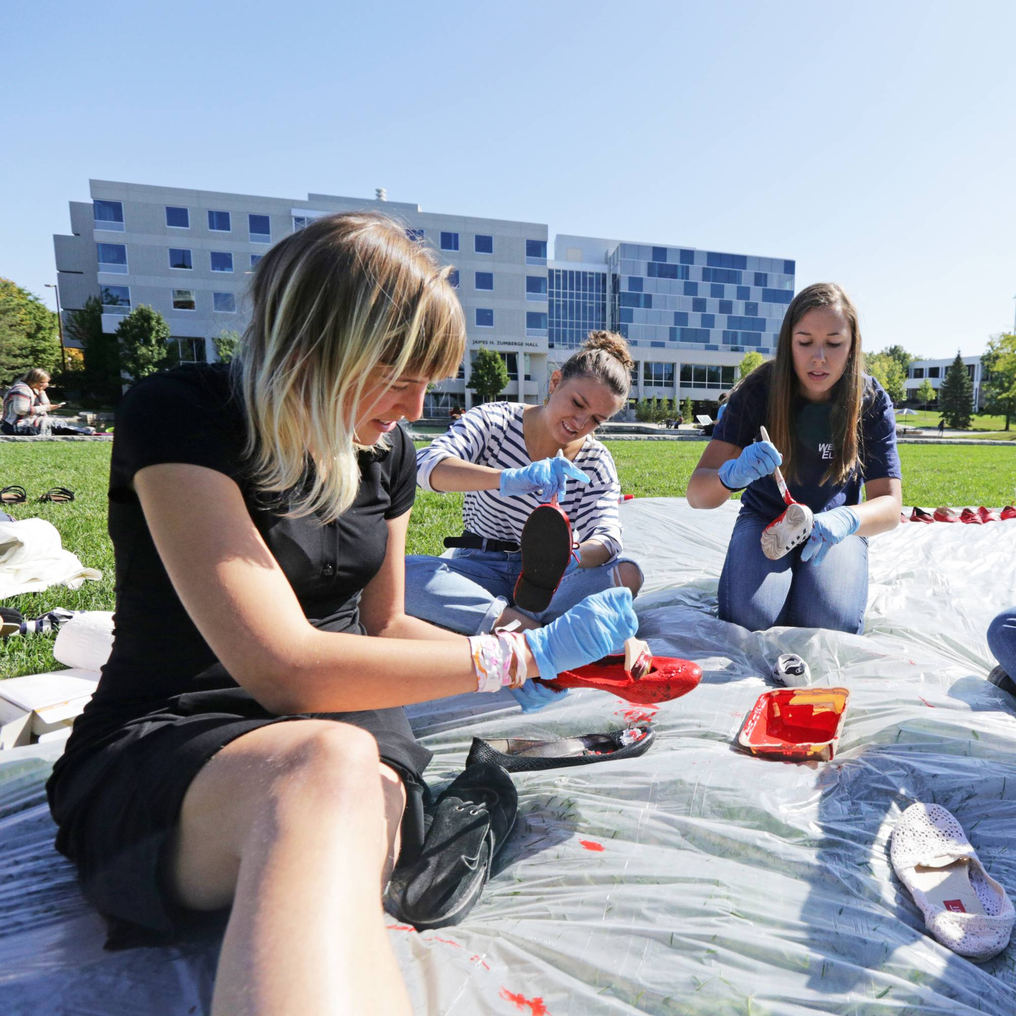 group of college students sitting on tarp in grass paying shoes red with brushes