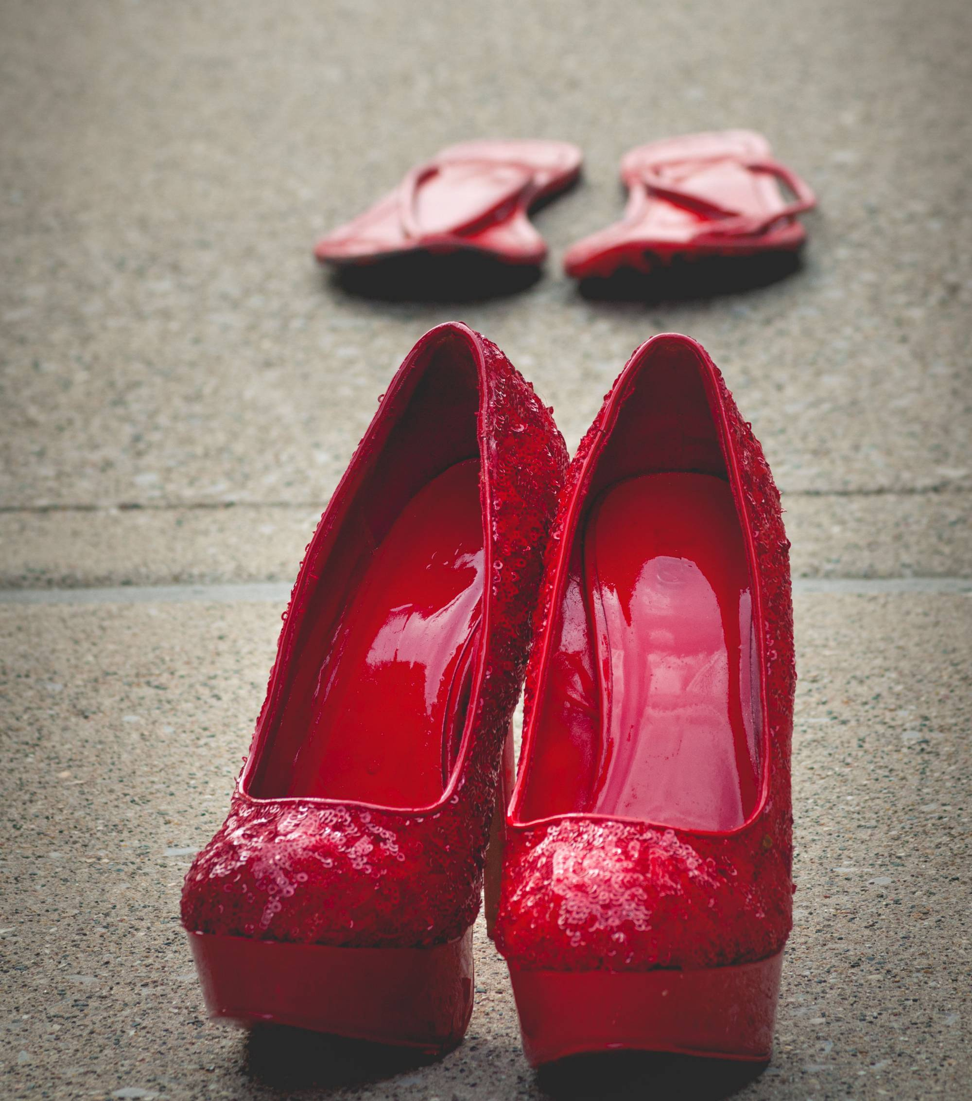 Pair of sequin heels painted red, sitting on pavement in courtyard