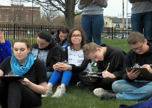 Students writing on their notes at a field day activity held by Michigan Environmental Education Curriculum Support (photo)