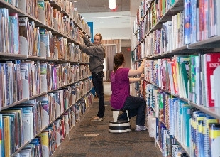 Students re-organizing bookshelves in the library (photo)