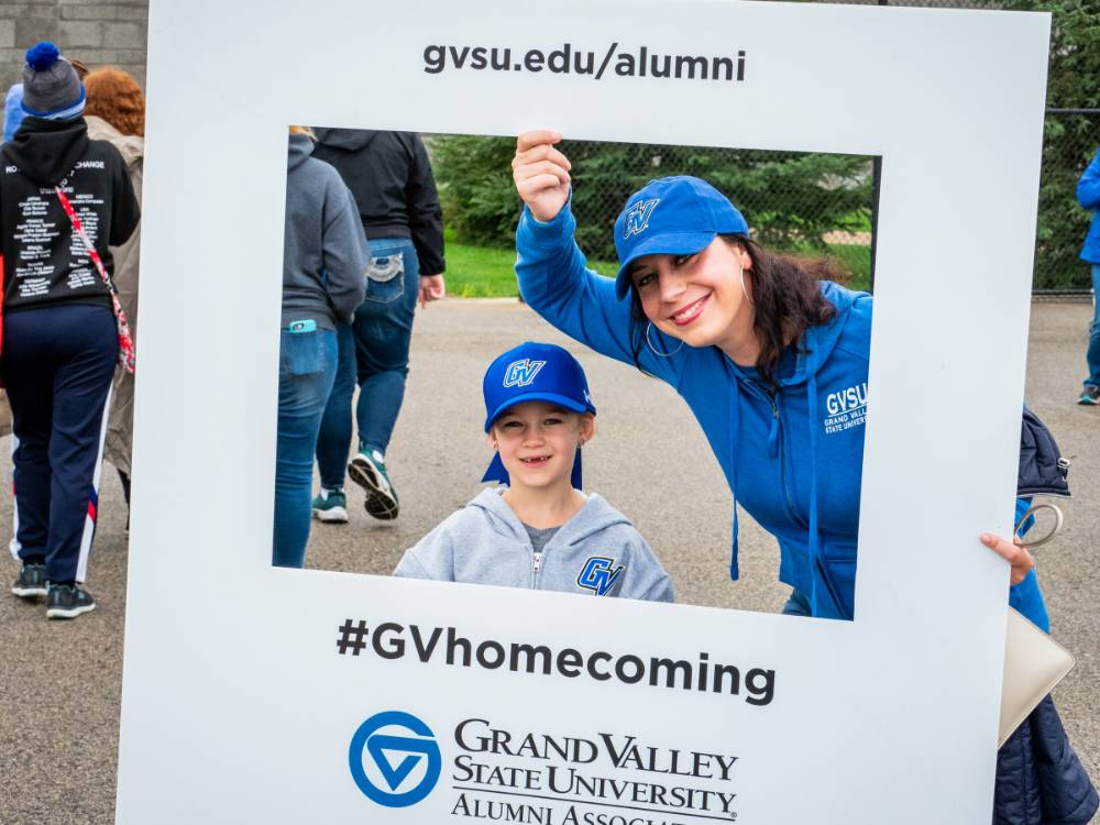 Alumna and little Laker pose with #GVhomecoming sign