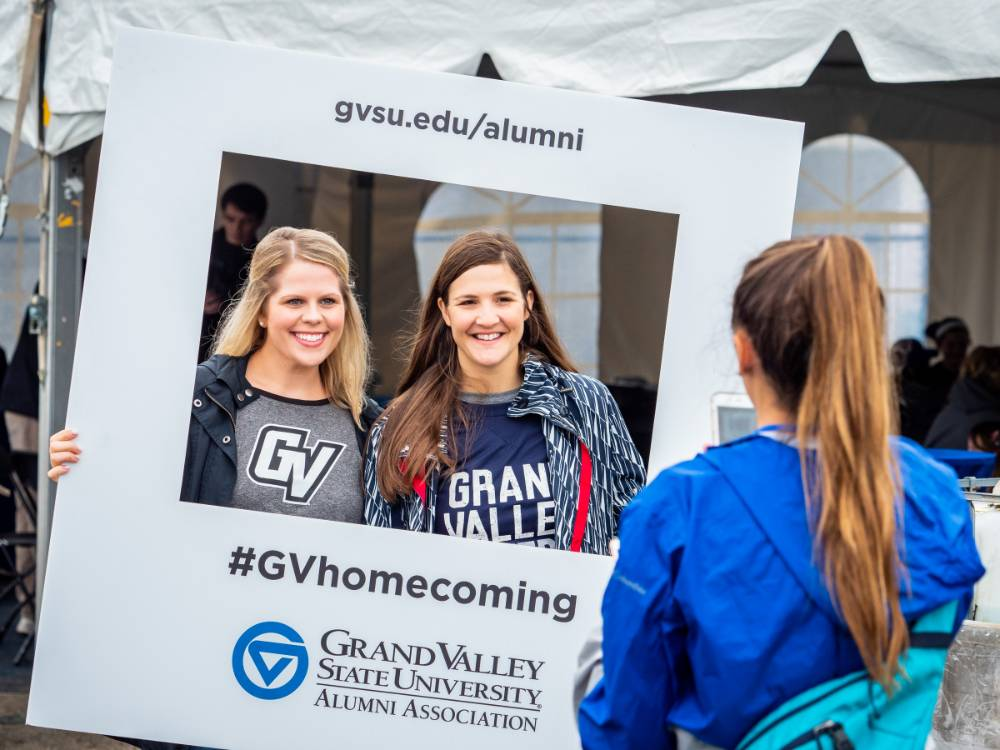 Alumnae pose with the #GVhomecoming sign